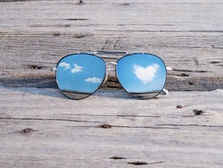 Reflection of blue sky and clouds heart shape in fashionable mirror sunglasses on vintage wood background. Happy summer vacation holiday concept.