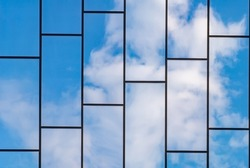 Reflection of blue sky with white clouds in windows of modern office building. Glass building with cloudy blue sky background.