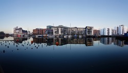 Reflection of buildings in the water at Port of Odense - panorama in cold tones.