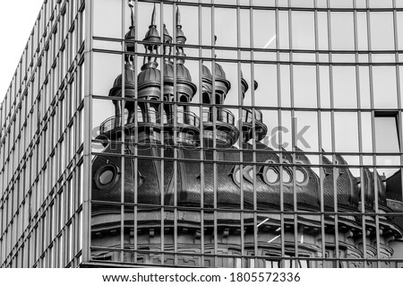 Reflection of chapel and bell tower in mirrored wall. Distorted reflection in glass panoramic windows. Black and white photo of corporate building exterior Foto stock ©