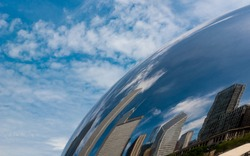 Reflection of Chicago buildings and the sky in the Chicago Bean Cloud Gate tourist attraction