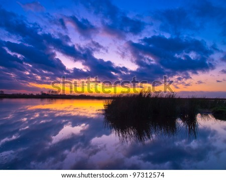 Reflection of clouded sky in wetland reserve during sunset - stock photo