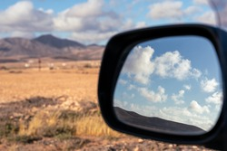 reflection of clouds in the rearview mirror of a car - selective focus
