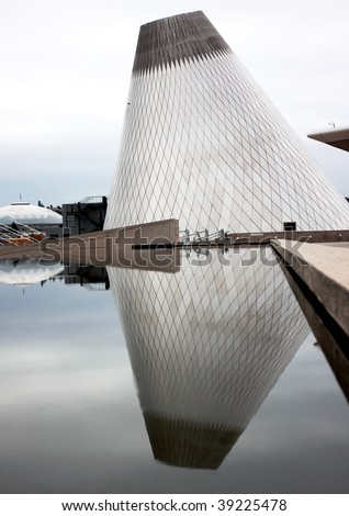 Reflection of conical shaped building in a pool of calm water