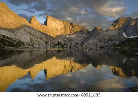 reflection of East Temple Peak and the Steeple in Deep Lake with evening alpenglow on the mountains, wind river range, wyoming