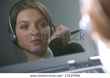 Reflection of face of female with headset holding pen in hand