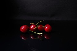 reflection of four cherries on black background