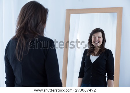 Reflection of girl wearing a fake smile #290087492
