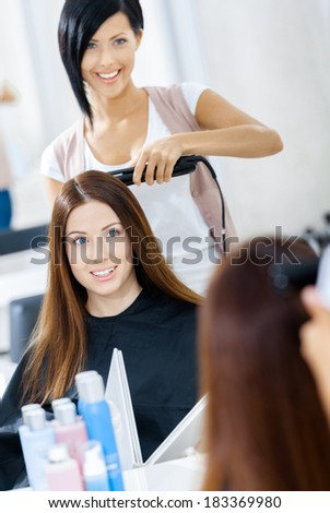Reflection of hairdresser doing hair style for woman in hairdress salon. Concept of fashion and beauty