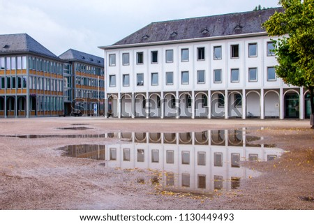 Reflection of houses near the Schlossplatz in Karlsruhe, next to the castle, reflecting in a puddle #1130449493