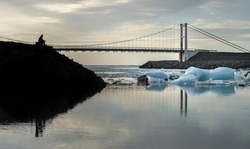 Reflection of ice cubes and hanging bridge with silhouette man foreground at  Jokulsarlon Glacier Lagoon during sunries