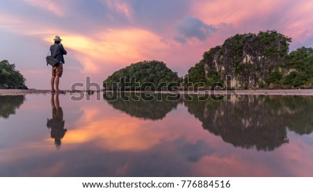 Reflection of man photographer take photo of summer landscape with beautiful sunset sky at Ao Nang Beach, famous tourist attraction and travel destination of Krabi Province, Thailand #776884516