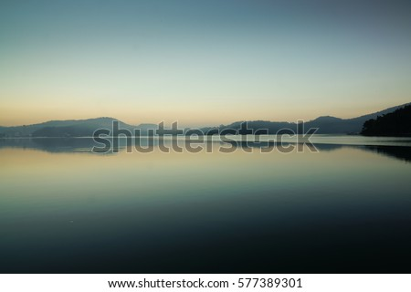 Reflection of mountain range in clear and still water at the Famous Sun Moon lake in Taipei depicting peaceful morning. This Beautiful landscape with Sunrise at dawn is a popular tourist attraction. Сток-фото ©