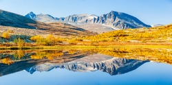 Reflection of mountains and trees in autumn landscape, Norway.