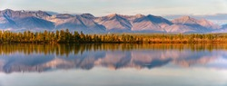 Reflection of mountains on a calm lake at sunset or sunrise. Panorama of autumn landscape in Yakutia, Sakha Republic, Russia. Beautiful scenery sunrise view of lake and reflection in water