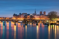 Reflection of Paris city in Seine river with Pont des Arts bridge foreground and Notre-Dame cathedral background during twilight, Paris, France