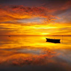 Reflection of Single Boat with Burning Sky During Sunrise/Sunset