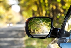 Reflection of  sunny autumn road at the car side mirrow.