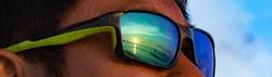 Reflection of sunset scene in green sunglasses