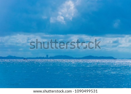 Reflection of the blue sea surface glittering. There are fishing boats, cityscape and mountains. #1090499531