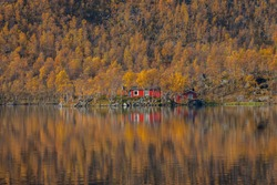 Reflection of the cottage and the autumn forest in the Mountain lake. Northern Norway. Tromso. Breivikeidet.