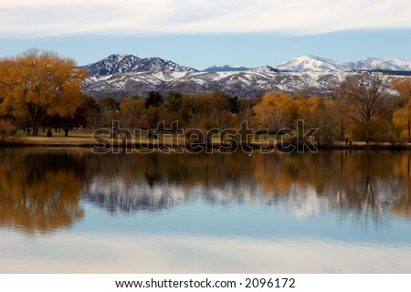 Reflection of the fall color, trees and mountains in the water. Focus is on horizon line.