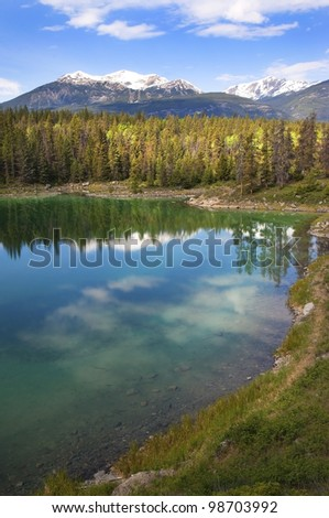 reflection of the forest and the sky in the emerald lake. Banff Alberta, Canada