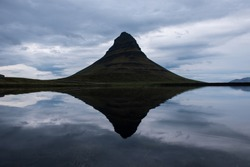 Reflection of the Kirkjufell mountain, one of Iceland iconic tourisitic destinations, in dark, sunset light. Snaefellsnes peninsula, Iceland