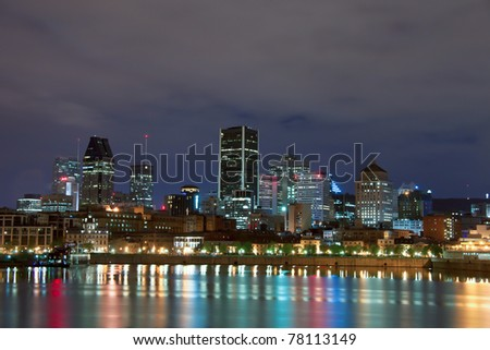 Reflection of the lights in the water of the St. Lawrence River, and Downtown Montreal in the background at night. - stock photo