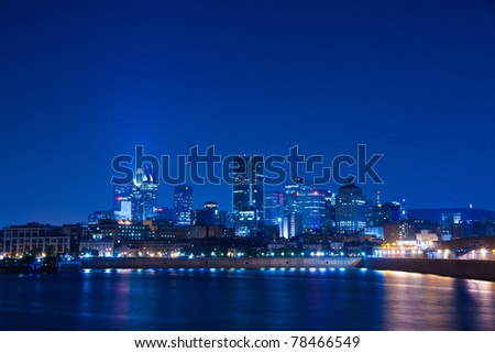Reflection of the lights in the water of the St. Lawrence River, and Downtown Montreal in the background at night (in Blue Tone Picture)