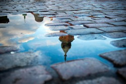 Reflection of the royal castle in a puddle on the cobblestones. Castle square in Warsaw old town, Poland