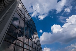 Reflection of the sky and clouds in the windows of a building .