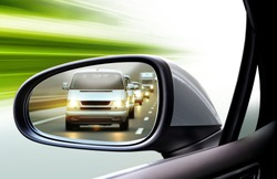 reflection of traffic flow in left side rear view mirror at twilight time