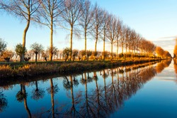 Reflection of trees boarding a canal at sunset in Damme near Bruges, West Flanders, Belgium.