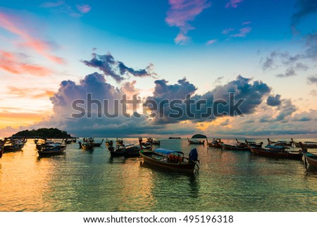 Reflection of Wooden Boat with Burning Sky During Sunrise in Andaman sea #495196318