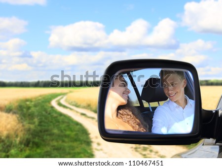 Reflection of young couple in mirror of car at countryside