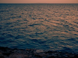Reflection on sea waves on dramatic sunset. Close up shot of dark red evening sinrise. Tripical ocean landscape