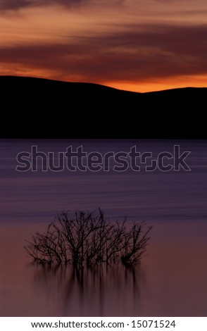 Reflection on silky smooth lake at sunset, under dramatic golden sky, long exposure