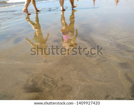 reflection on the water of the sand of a beach of a tropical seashore during a low tide showing the feet of several persons walking and the reflection of their bodies on the sea water. Horizontal pic