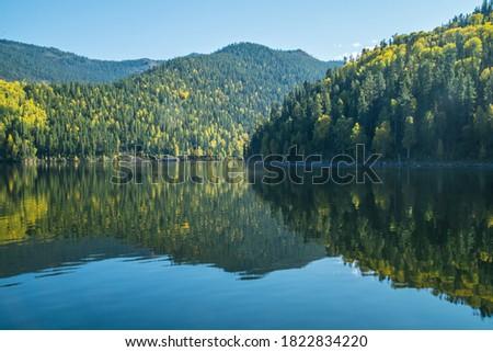 Photo of  Reflection on the Yenisei River, autumn view. Sayano-Shushenski Nature Biosphere Reserve. Wild place in Siberia, Krasnoyarsk region.