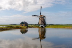 Reflection on water of traditional Molen Het Noorden (Windmills The North) is a polder mill of Texel Island, Dutch landscape under blue sky and white clouds, Noord Holland, Oosterend, Netherlands.