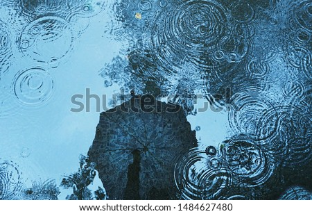 reflection umbrella in puddle background. rain backdrop. autumn season, wet weather, rainy day, fall time concept. copy space Foto stock ©