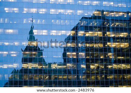 Reflections from a glass building at dusk with the illuminated offices still visible. - stock photo