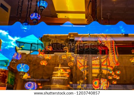 Reflections in a window in downtown Santa Fe showing a very blue sky and Turkish lanterns and adobe architecture