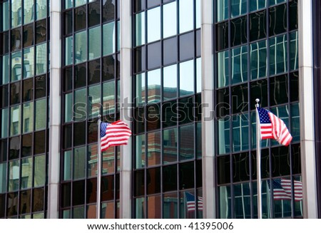 Reflections in an office building with flags also flying and reflected.