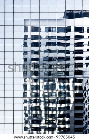 Reflections of a building in the glass facade of another one. Reflections in a blue glass skyscraper - stock photo