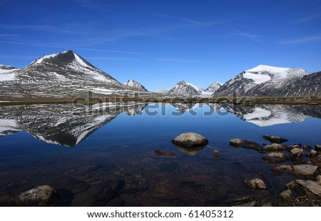 Reflections of arctic mountains in an lake, Sweden.