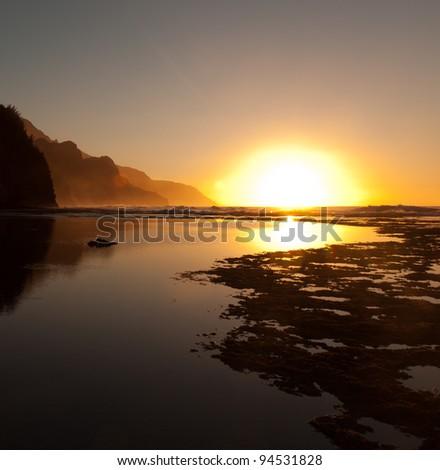 Reflections of setting sun over Na Pali coast by Ke'e beach in Kauai at sunset
