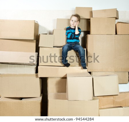 Reflective child sitting on the top of heap of carton packed boxes.