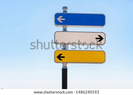 Reflective traffic signal with three direction indicator panels with blue sky